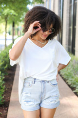 White - Model wearing the Oversized Satin Top with distressed mom shorts