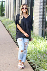 Model wearing the Oversized Satin Top in Black with distressed boyfriend jeans