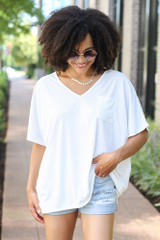 Model wearing the Oversized Satin Top in White with distressed denim shorts