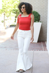 Model wearing the Smocked Tie-Strap Tank in Red with white flare jeans