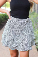 White - Dress Up model wearing the Spotted Wrap Skirt with a black bodysuit