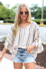 Model wearing a Striped Blouse with denim shorts