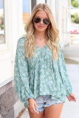 Model wearing the Floral Babydoll Blouse with denim shorts