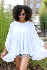White - Model wearing a Tiered Oversized Blouse with distressed denim mom shorts