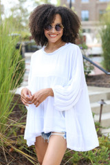 White - Dress Up model wearing a Tiered Oversized Blouse with denim shorts