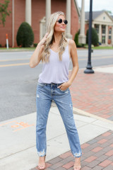 Model wearing the Sweater Tank in Lilac with distressed straight leg jeans and nude heels