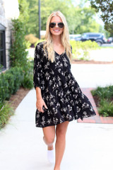Model wearing a Floral Babydoll Dress in Black with white slip-on sneakers