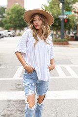 Model wearing a Striped Babydoll Top with distressed boyfriend jeans and a straw sun hat