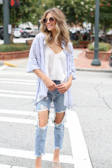 Model wearing a Striped Oversized Blouse with distressed boyfriend jeans