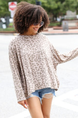 Model wearing an Oversized Leopard Top with denim shorts