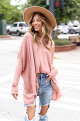 Model wearing an Oversized Ribbed Knit Top with distressed boyfriend jeans and a wide brim hat