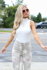 Model wearing a Mock Neck Bodysuit in Ivory with star flare jeans