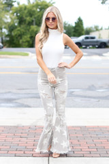 Model wearing Distressed Star Flare Jeans with a white bodysuit