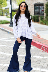 Model wearing a Plaid Babydoll Top with dark wash flare jeans