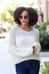 Ivory - Model wearing an Oversized Loose Knit Sweater with dark wash jeans