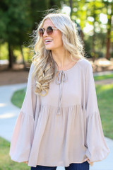 Taupe - Model wearing an Oversized Babydoll Blouse with flare jeans
