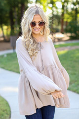 Taupe - Dress Up model wearing an Oversized Babydoll Blouse with flare jeans