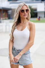 White - Model wearing a Cami Bodysuit with denim shorts