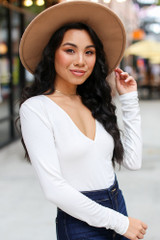 White - Dress Up model wearing a V-Neck Bodysuit with flare jeans