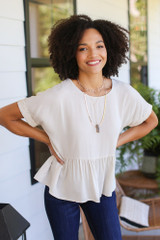 Model wearing a Oversized Peplum Blouse with a gold layered necklace