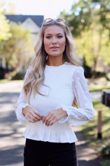 Dress up boutique model wearing a white smocked top