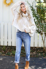 Model wearing Mom Jeans with a cable knit sweater and booties