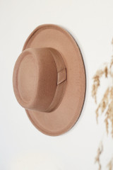 Wide Brim Hat in Nude hanging on a white wall