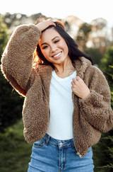 Dress Up model wearing a tan Cropped Sherpa Jacket with light wash denim