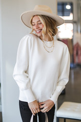 Ivory - Model wearing a Puff Sleeve Sweater with black jeans