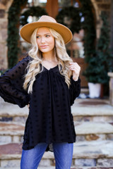Model wearing a Swiss Dot Babydoll Blouse with a wide brim hat