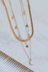 Flat Lay of a Gold Star + Moon Layered Necklace
