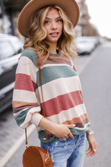 Model wearing an Oversized Striped Pullover with a wide brim hat
