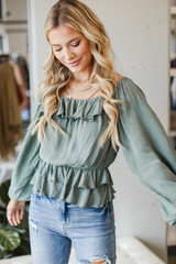 Model wearing a sage Ruffled Blouse