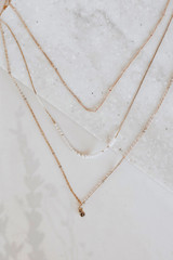 Flat Lay of a Gold Pearl + Rhinestone Layered Necklace