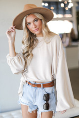 Taupe - Model wearing a Brushed Knit Tie-Front Top in Taupe with a wide brim hat