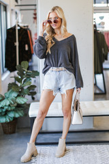 Model wearing a Ribbed Knit Pullover in Black with denim shorts