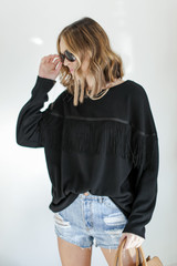 Model wearing a Fringe Pullover with denim shorts