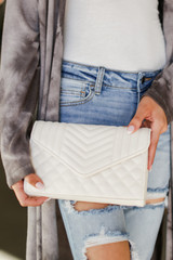 Model carrying a Quilted Crossbody Bag in Ivory