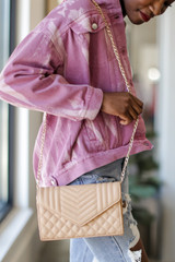Model carrying a Quilted Crossbody Bag in Nude