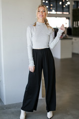 Model wearing Wide Leg Pants in Black with a mock neck crop top
