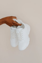 Model holding white Knit Sneakers