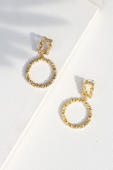 Flat Lay of Textured Gold Drop Earrings