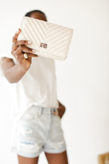 Model holding a Quilted Crossbody Bag in Ivory