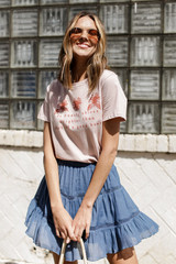 Model wearing the Good Heart Floral Graphic Tee with a mini skirt