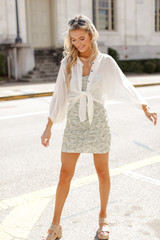 Model wearing a Ruched Floral Mini Dress with a white linen blouse