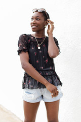 Model wearing a Mesh Floral Top with denim shorts