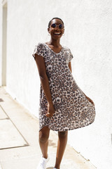 Dress Up model wearing a Leopard T-Shirt Dress with chunky white sneakers