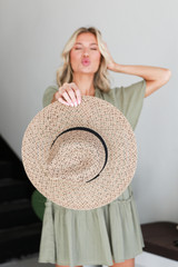 Model holding a Straw Fedora Hat in Taupe