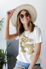 Model wearing the Here Comes the Sun Vintage Graphic Tee with a straw hat