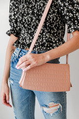 Model carrying a Crocodile Crossbody Bag in Pink